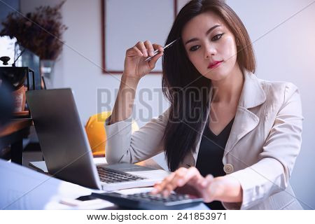 Young Asian Women With Laptop And Calculator Counting Make Notes At Coffee Shop,hand Writing In Note