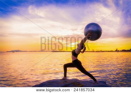 Silhouette Of Young Asian Woman Practicing Yoga On The Beach At Sunset.relaxing,healthy Concept.