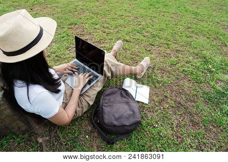 Young Hipster Woman Using Laptop While Sitting In Park With Bag And Blank Notebook.
