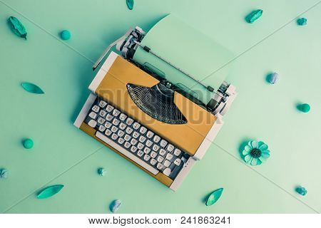 Flat Lay Of Yellow Retro Typewriter Against Green Flower Pattern Background Minimal Creative Concept