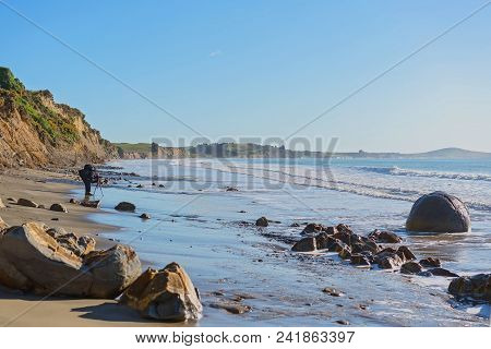 Distant Shape Of A Photographer Taking Shots Of The Unusual Geological Formation Of The Moeraki Boul