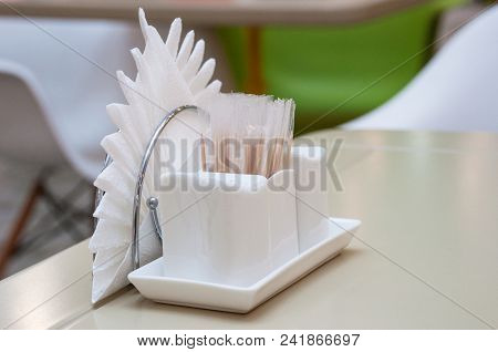 White Ceramic Pepper And Salt Shaker Stand On A Table In A Cafe Together With Paper Napkins And Disp