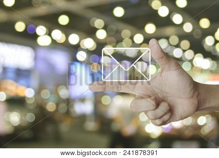 Mail Icon On Finger Over Blur Light And Shadow Of Shopping Mall, Contact Us Concept