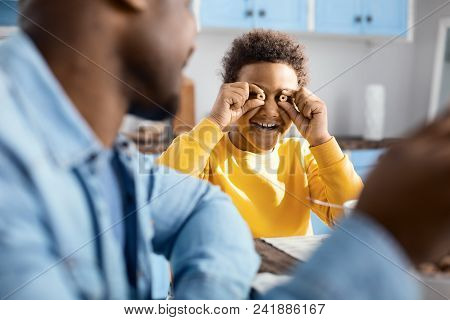 Upbeat Mood. The Focus Being On A Cheerful Curly-haired Boy Goofing Around During Breakfast And Smil