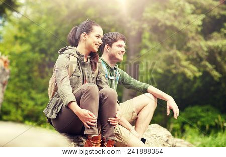travel, hiking, backpacking, tourism and people concept - smiling couple with backpacks resting in nature