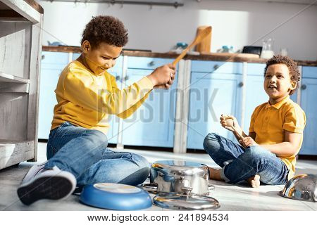 Little Music Lovers. Upbeat Little Boys Playing Music On Saucepans With Wooden Spoons And Having Fun