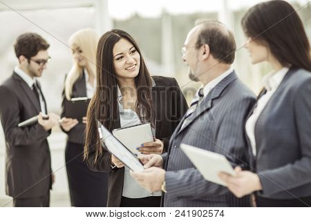 Employees Discuss Their Goals Before The Start Of The Workshop Standing In The Lobby Of A Modern Off