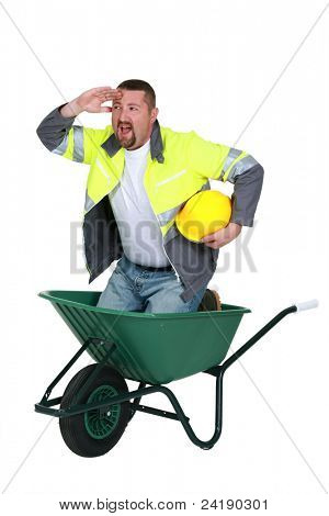 Construction worker in a wheelbarrow