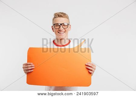 Photo of modern youngster wearing casual clothing and glasses holding blank orange banner in hands isolated over white background