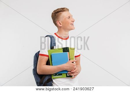 Image of thin teenage man university or college student wearing backpack looking aside at copyspace while holding textbooks isolated over white background