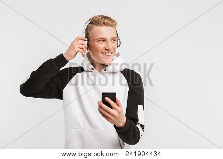 Portrait of caucasian youngster 16-18 years old wearing hoodie smiling and listening to music on mobile phone via wireless earphones isolated over white background