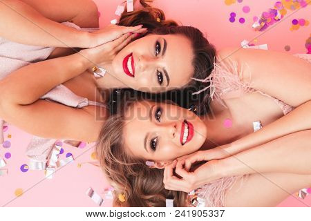 Horizontal image of party girls in dresses smiling and lying on the floor with heads in opposite directions under falling colorful confetti isolated over pink background