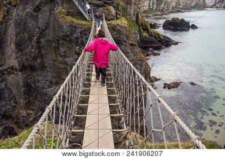 People Crossing The Carrick-a-rede Rope Bridge, Antrim Coast.