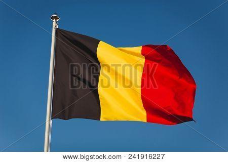 Flag Of Belgium On Mast. National Flag Against Wind Blue Sky. Flag Of Belgium, Capital Bruxelless. N