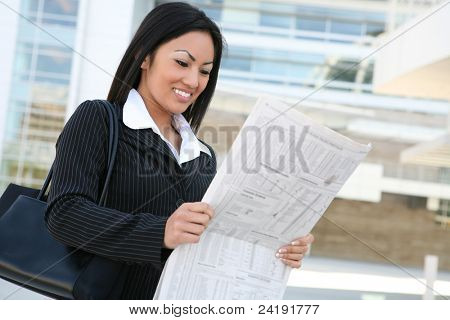 A pretty asian business woman reading the newspaper outside company