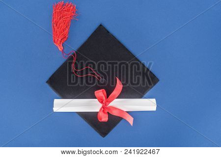 Graduation Hat And Diploma With Red Ribbon Isolated On Blue