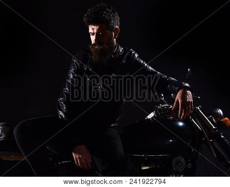 Macho, brutal biker in leather jacket stand near motorcycle at night time. Brutality and masculine concept. Man with beard, biker in leather jacket lean on motor bike in darkness, black background. poster