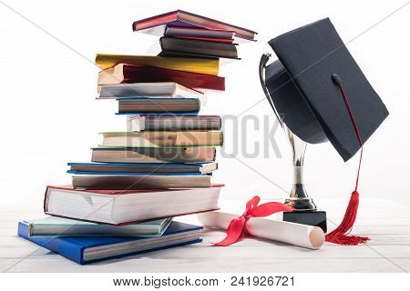 Graduation Cap On Trophy Cup By Books And Diploma On Table