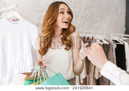 Excited young couple shopping for clothes together at the clothing store, woman holding lots of shopping bags and man giving credit card