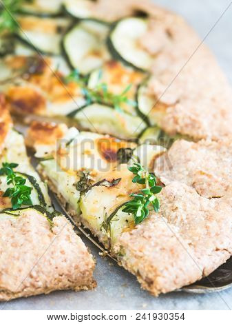 Savory Zucchini And Cheese Galette On Spelt Dought, Served With Fresh Thyme.