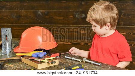Side View Kid Grabbing Screwdriver. Boy Playing With Long Metal Bolts And Screw Nuts. Informal Educa