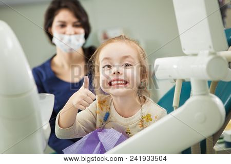 Cheerful Kid With Broad Smile After Painless Teeth Polishing Procedure Sits In Comfortable Chair At