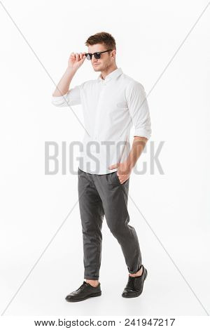 Full length portrait of a confident young man in sunglasses walking isolated over white background