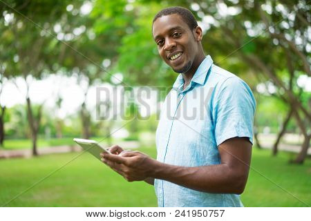 Happy Confident Handsome Young African Man Using Tablet While Walking In Summer Park. Cheerful Guy I