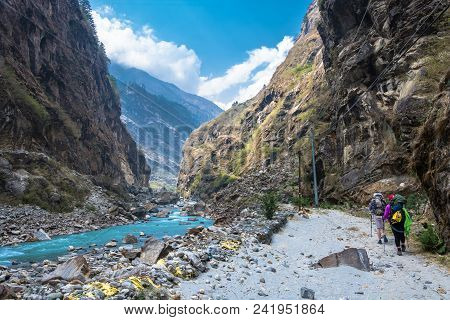 Two Tourists Walk Along A Mountain Road Along The Bank Of A Mountain River In Nepal.