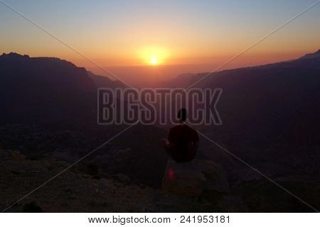 Sitting Relaxed Young Man During Sunset In Canyon Of Dana Biosphere Nature Reserve Landscape Near Da