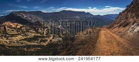 Picturesque Overlook Of Calabasas Peak Trail Winding Through The Canyon With Rock Formations On A Su