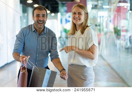 Smiling Woman Pointing At Purchase In Paper Bag Held By Husband In Mall With Glass Walls In Backgrou