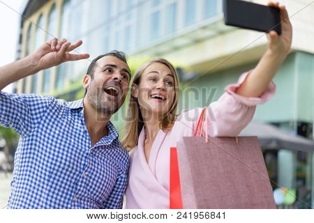 Couple Of Happy Shoppers Freaking Near Shopping Mall. Careless Woman And Her Joyful Boyfriend With P