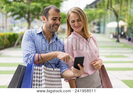 Happy Stylish Couple Using Mobile App For Shopping. Smiling Man And Woman With Shopping Bags Walking