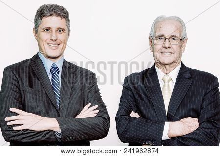 Confident Senior Entrepreneur And His Son With Crossed Arms Looking At Camera. Caucasian Colleagues