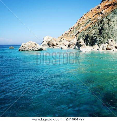 Rocky Shore. Southern Coast Of Turkey. Calm Blue Sea And Clear Sky. Small Beach On The Island Near A