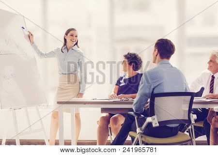 Cheerful Young Businesswoman Pointing At Whiteboard And Explaining Strategy. Confident Business Coac