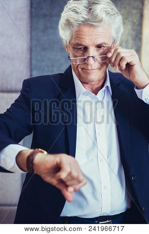 Serious Senior Businessman Lowering Eyeglasses And Checking Time. Busy Man Being Late Or Waiting For