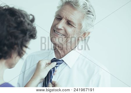 Wife Adjusting Tie Of Her Cheerful Husband. Woman Helping Her Husband To Get Ready For Work. Relatio