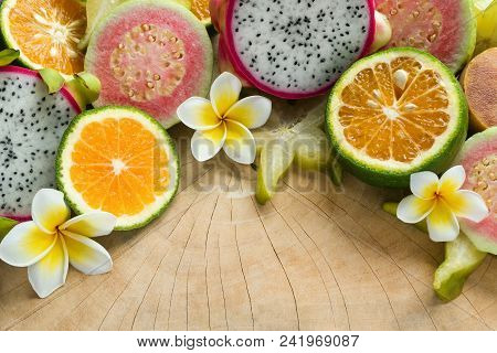 Bright Colorful Tropical Fruits (tangerine, Guava, Dragon Fruit, Star Fruit, Sapodilla) With Flowers
