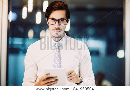 Portrait Of Serious Young Caucasian Businessman Wearing Glasses Standing In Office Holding Touchpad
