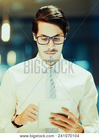 Portrait Of Serious Young Caucasian Businessman Wearing Glasses Working Late In Office With His Touc