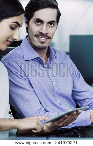 Young Caucasian Businessman Sitting On Office With Female Colleague Holding Touchpad And Showing Som