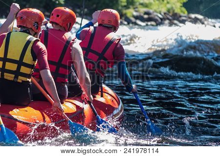 Rafting In Life Jackets, Men Row Oars On A Catamaran. Extreme Sports In A Mountain River.
