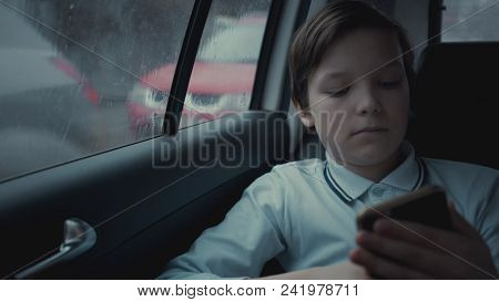 Sad, Unhappy Young Boy Riding In Car Through City During Rainy Day, Using Social Network On His Smar