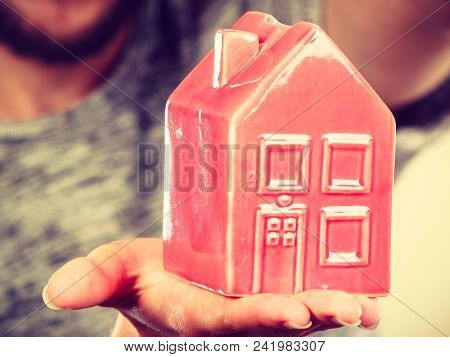 Household, Housekeeping Concept. Man Holding Tiny Red Statue In Shape Of House. Indoor Shot