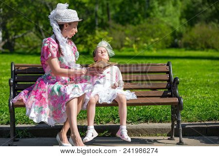 Mother And Daughter In A Summer Park.