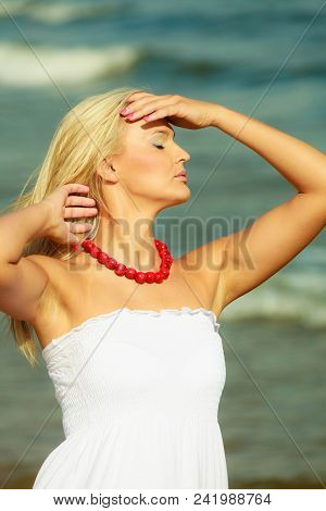 Rest And Relax Concept. Attractive Gorgeous Blonde Woman Wearing White Dress Resting On Fresh Air On