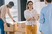 multiethnic coworkers carrying cardboard boxes during relocation in new office poster
