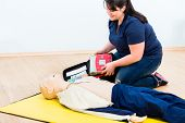 First aider trainee learning revival with defibrillator in first aid course poster